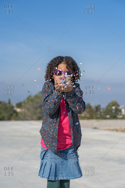 African-American girl with curly hair playing with confetti