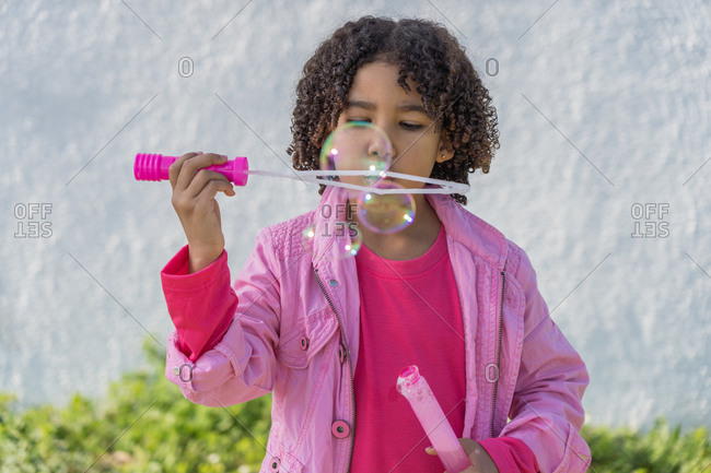 Little African-American girl with curly hair dressed in pink playing with soap bubbles