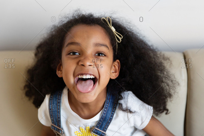 Smiling young girl with afro hair sticking tongue