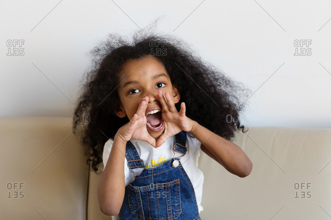 Happy little girl shouting with hands around mouth