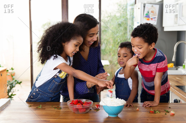 Happy family eating Strawberries and cream in kitchen