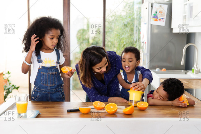 Mother helping toddler boy prepare orange juice in kitchen
