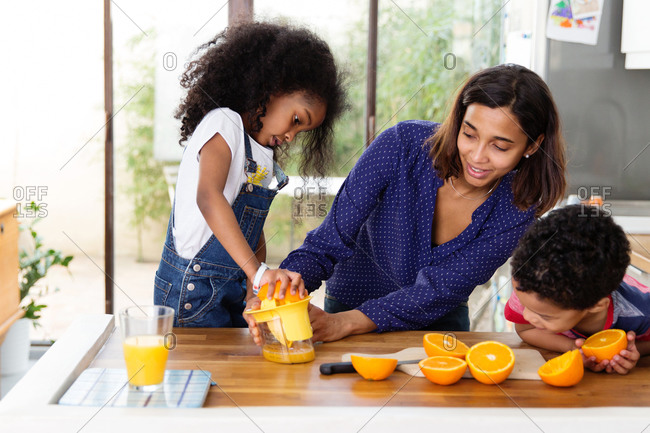 Mother helping daughter prepare orange juice in kitchen