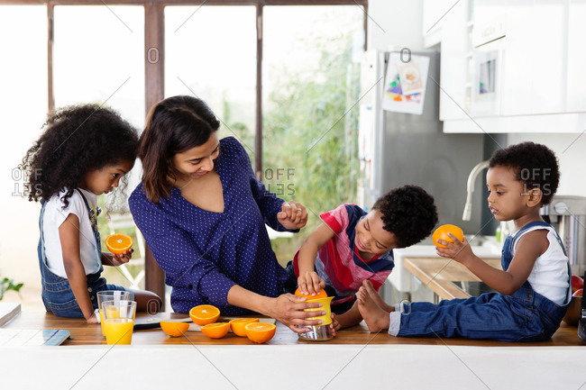 Mother teaching her kids how to prepare home made orange juice