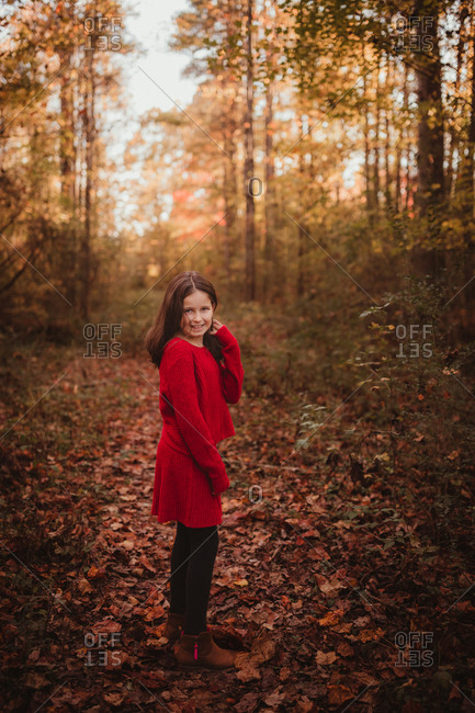 Girl in red walking through forest
