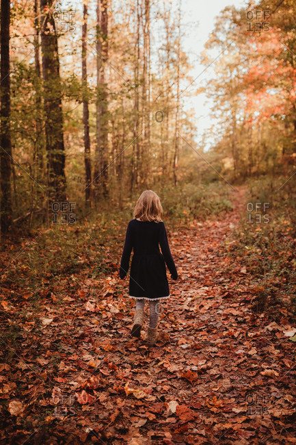 Blonde girl taking a walk in the forest