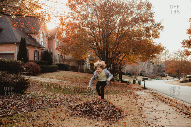Girl jumping onto a pile of leaves in her neighborhood