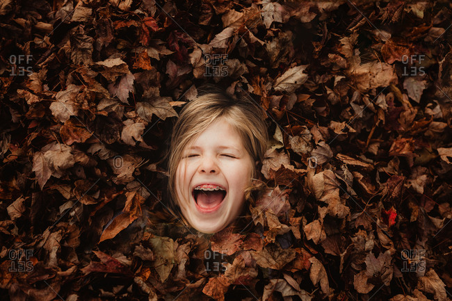 Close up of a girl lying in a pile of leaves