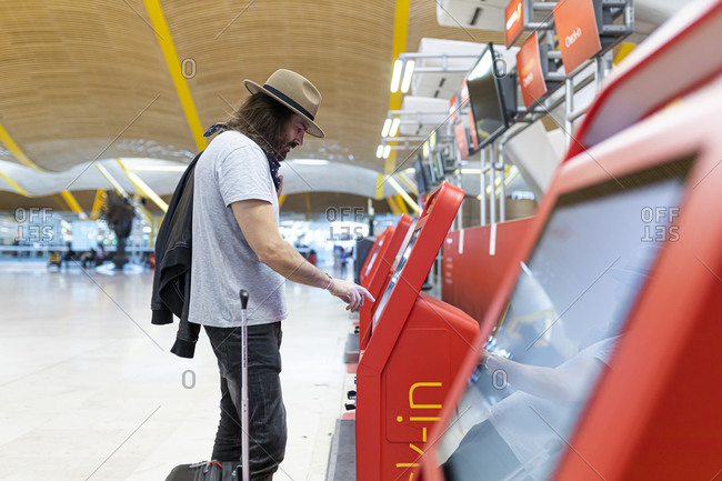 Young man with beard and long hair buying airline tickets at the airline's automatic terminal