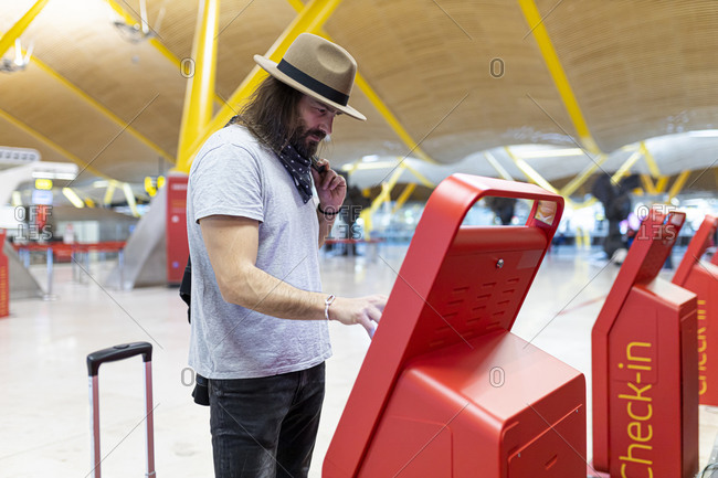 Young man with long hair and hat buying airline tickets at the airline's automatic terminal