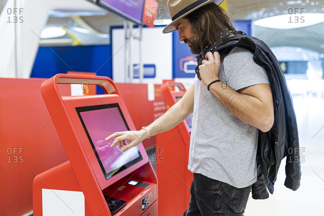 Young man with beard buying airline tickets at the airline's automatic terminal