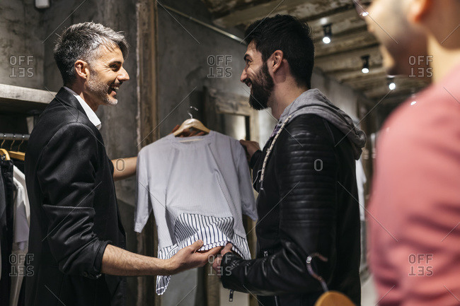 Designer in modern menswear shop offering new collection to man