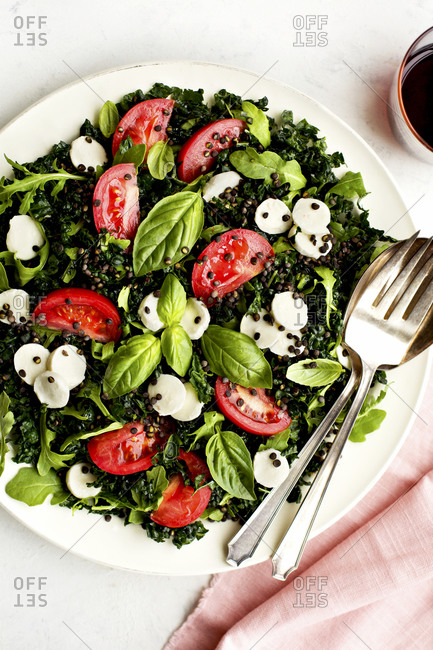 Kale Caprese Salad with Crispy Black Lentils and Arugula Vinaigrette set on a white table with a pink napkin and fork and spoon.