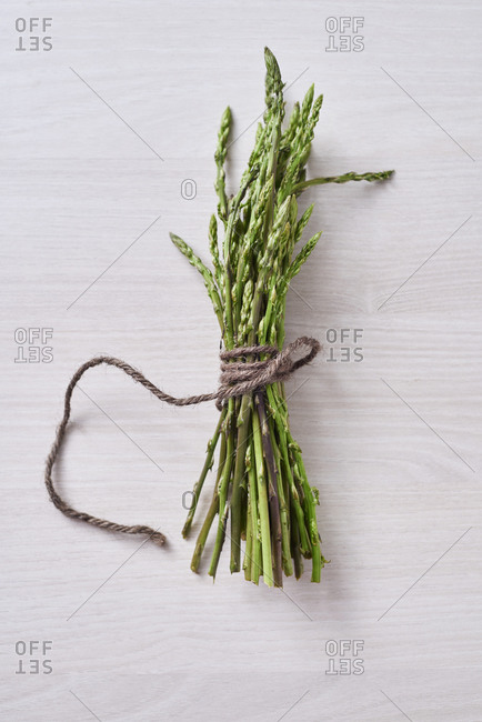 High angle view of a bunch of raw wild asparagus tied with a string on a white wooden surface