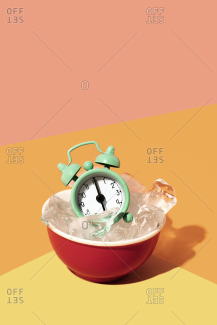 Green alarm clock in a red bowl with ice cubes, on a yellow, orange and pink background, depicting the idea of freezing time
