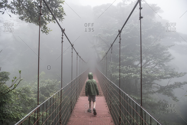 A boy walks across a bridge in the Monteverde Cloud Forest