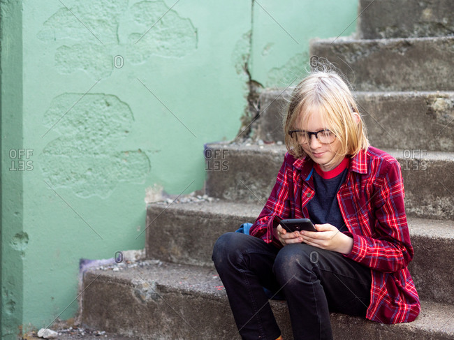 Tween smiling sitting on stairs using smartphone