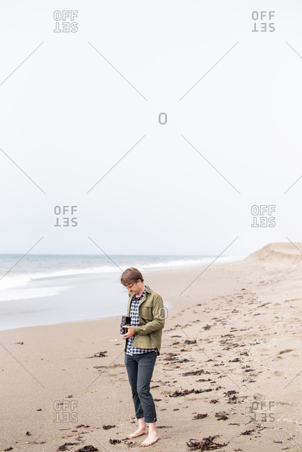 Young man standing on beach taking photograph with film camera
