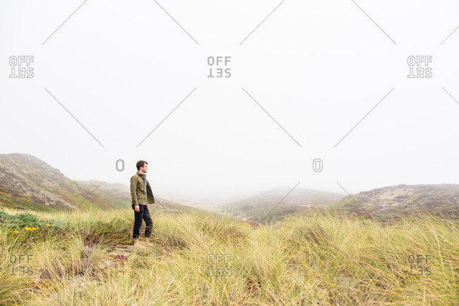 Young man standing in field of sea grass on the coast