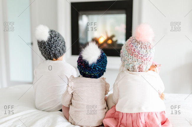 Three toddlers sitting on bed in front of fireplace with knit hats