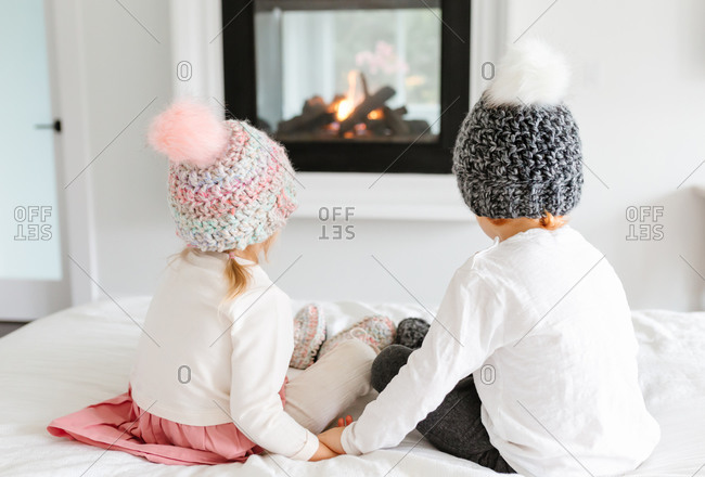 Two toddlers holding hands in front of fireplace with knit hats