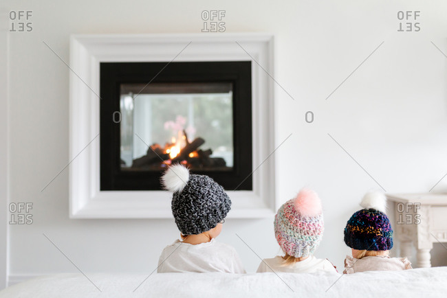 toddlers sitting in front of a fireplace with toque knit hats