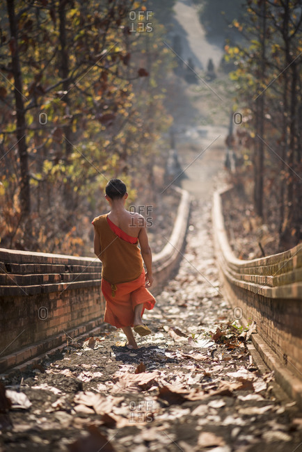 A young Buddhist monk climbing the stairway leading to Wat Phra Non temple in Mae Hong Son, Thailand.