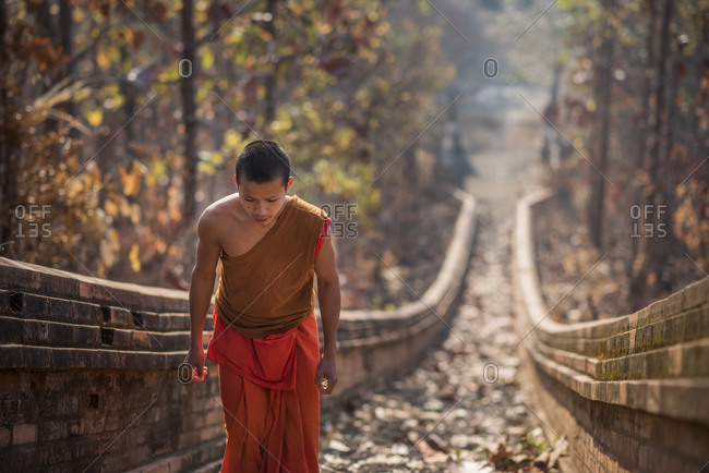 Mae Ho, Mae Hong Son, Thailand - February 28, 2015: A young Buddhist monk climbing the stairway leading to Wat Phra Non temple in Mae Hong Son, Thailand.