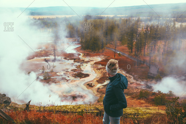 Woman tourist overlooking geyser at Yellowstone National Park