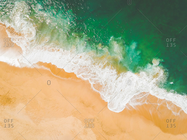 Aerial drone view of beach and sea waves crashing