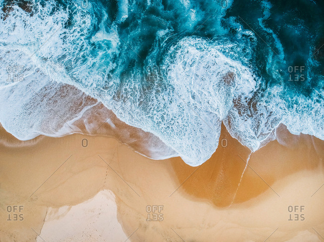 drone aerial view of ocean surf crashing on empty beach blue