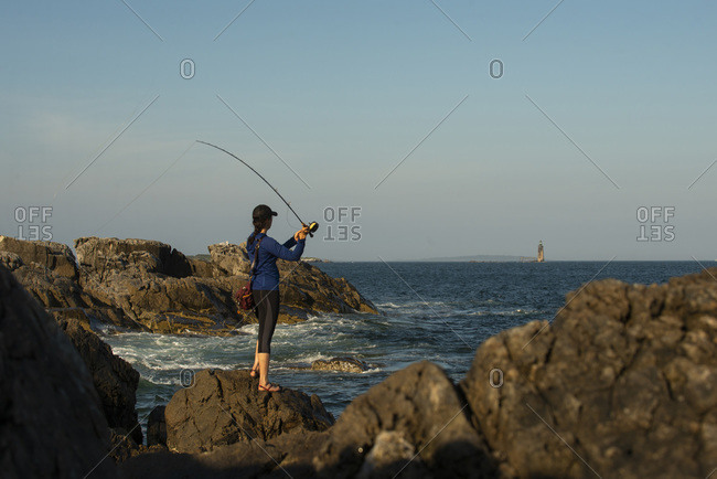 Woman fly fishing on the coast of Maine on a sunny day.