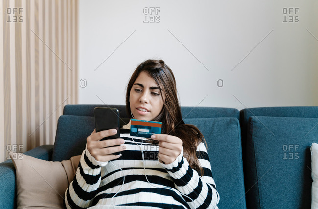 young girl paying with the credit card while using the smartphone