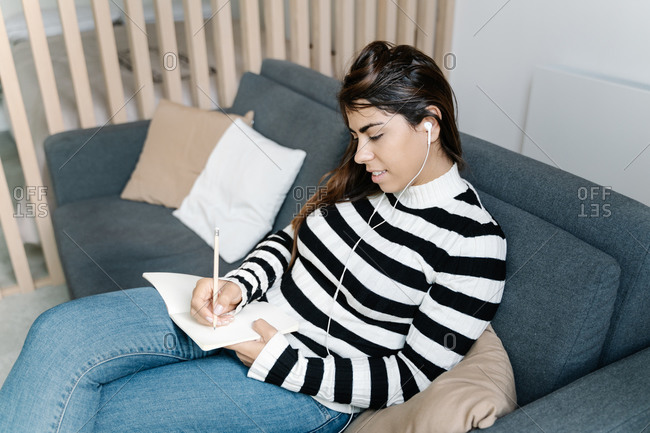 Young girl sitting on a sofa and taking some notes in a notebook