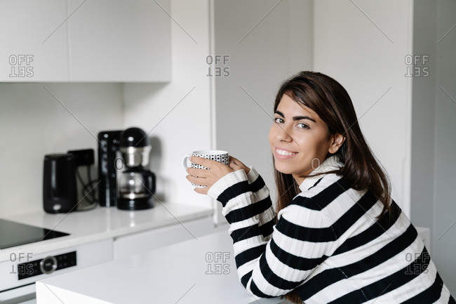 young beautiful girl sitting in a cozy kitchen while holding a cup