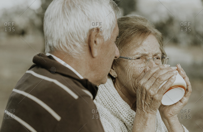 Older woman drinking coffee while her husband looks at her