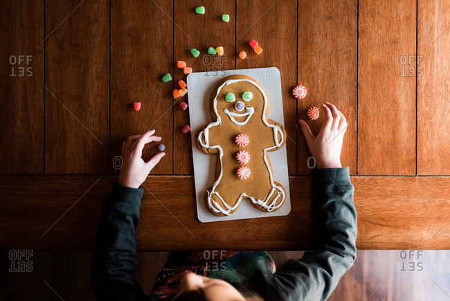 Small kid decorating a gingerbread man on the kitchen table