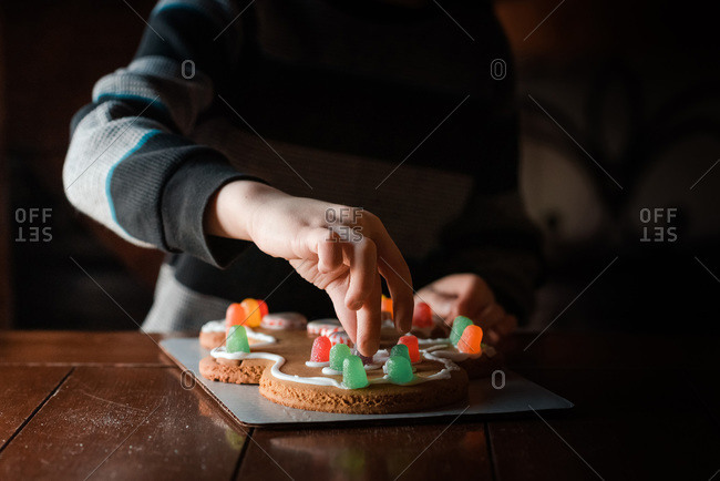 small hands touching a gumdrop on a gingerbread man cookie on table