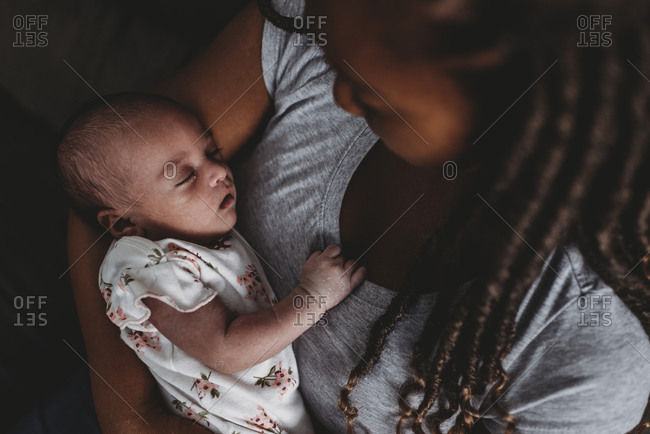Precious multiracial infant peacefully sleeping in mother's embrace