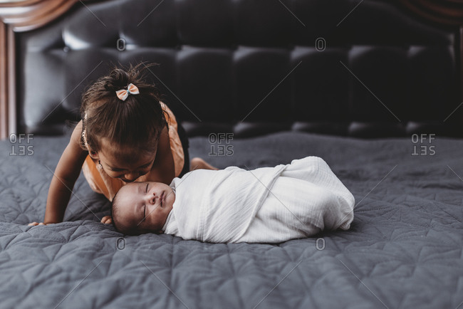 Sweet multiracial 2 yr old girl on bed with swaddled infant sibling