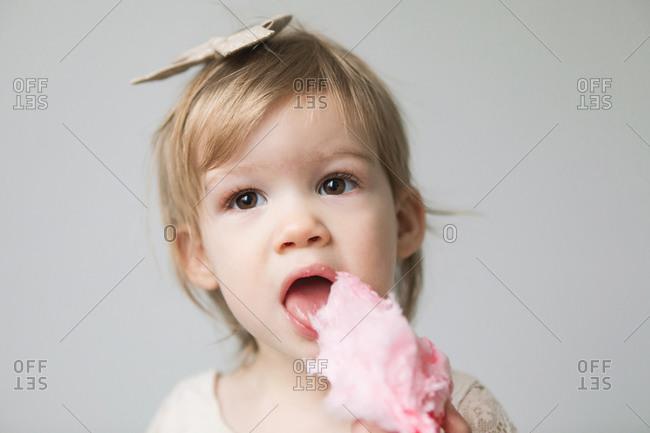 Toddler eating pink cotton candy