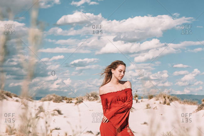 Twenty year old woman in a red dress in the desert