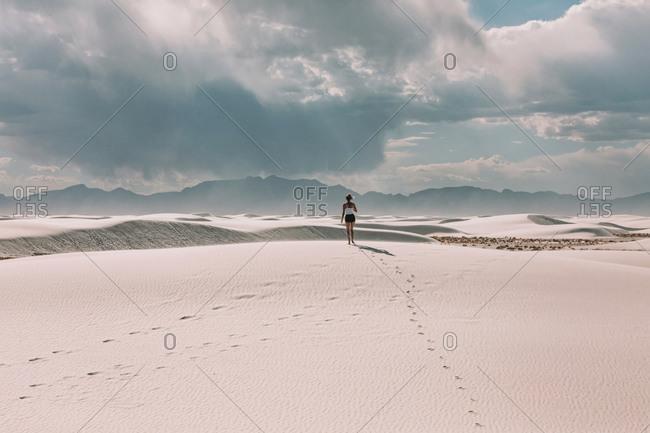 woman walking in the desert as the sun shines through a cloud