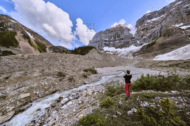 A woman stops to take a photo of glacial runoff above Cirque Lake.