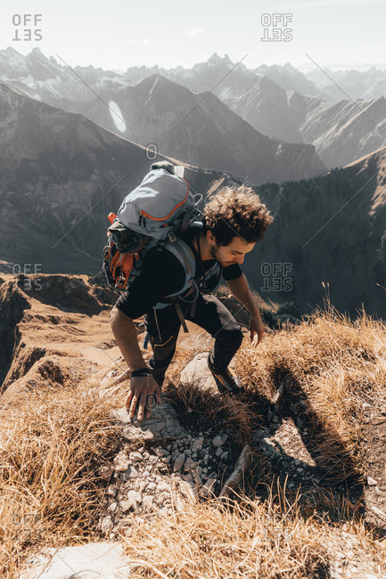 Young hiker climbing steep trail in front of alpine background