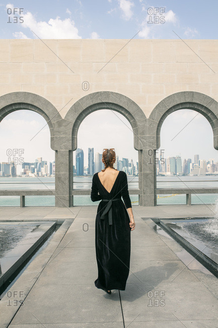 Back view of young woman walking and looking at the sea in Doha