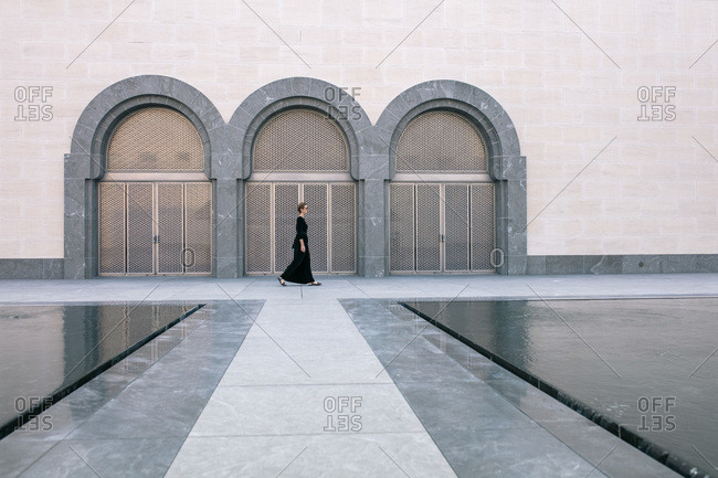 Woman walking by the arch gates in Museum of Islamic art in Doha