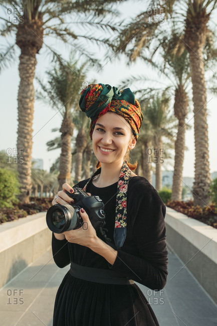 Portrait of smiling  young woman with headwrap holding her camera