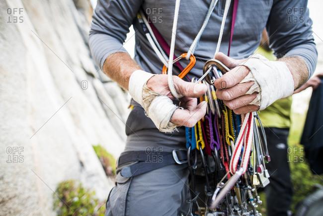 Rugged climber hands sorting through climbing gear