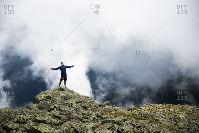 Male hiker enjoying the sun in the mountains with clouds behind
